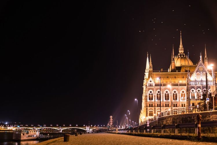 Hungarian parliament building by road against sky in city at night