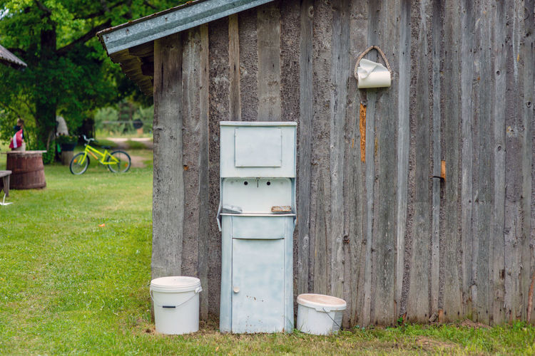 At the farmhouse outbuildings walls arranged Old fashioned rustic washstand. Farm Farmhouse Rural Rustic Absence Architecture Bathroom Bench Building Building Exterior Built Structure Container Day Front Or Back Yard Grass Green Color Nature No People Old Outdoors Plant Seat Tree Washstand Wood - Material