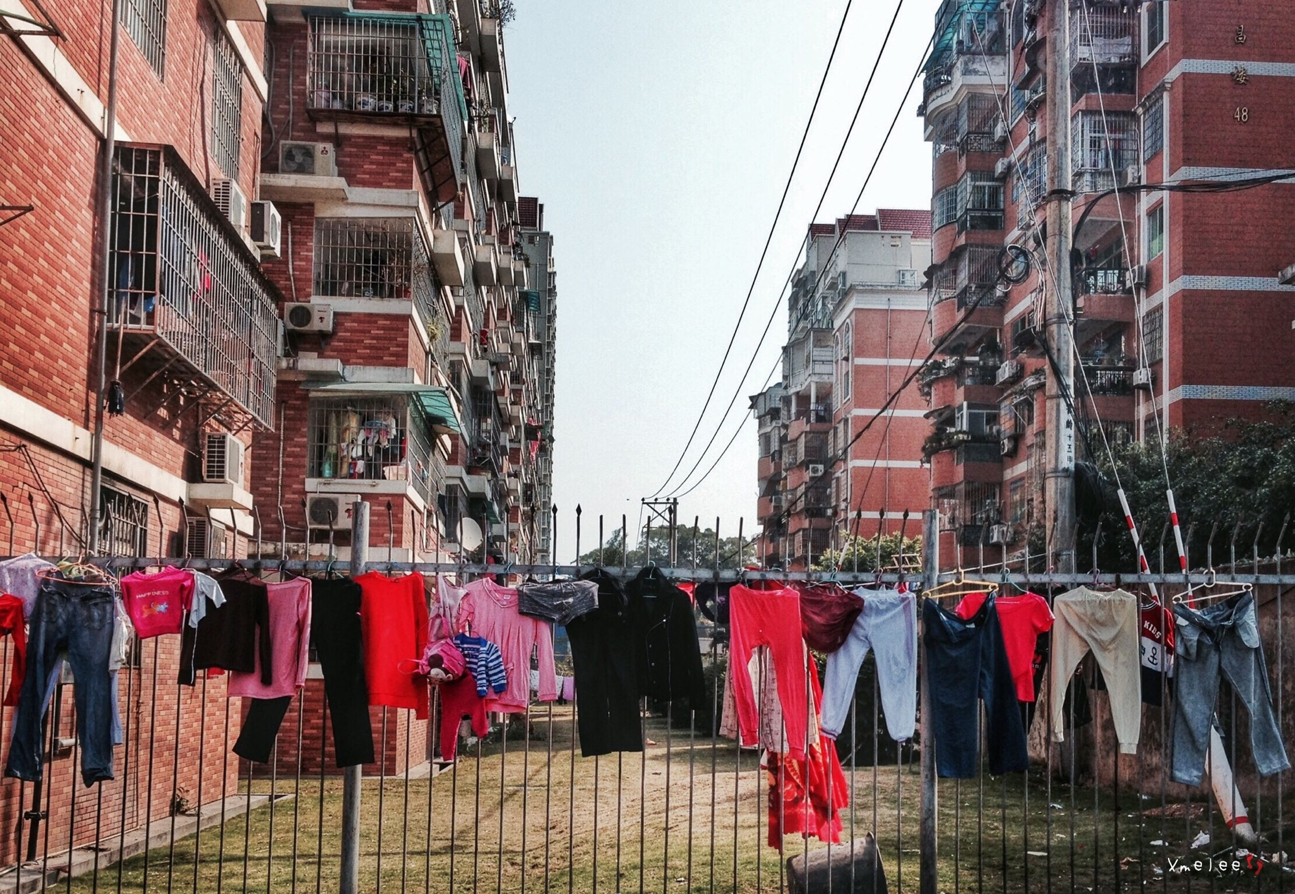 building exterior, architecture, built structure, men, person, large group of people, city, walking, street, building, lifestyles, drying, flag, city life, day, clothing, residential structure, market, residential building
