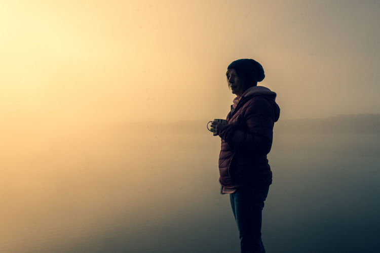 Side view of woman standing by lake against sky during dawn
