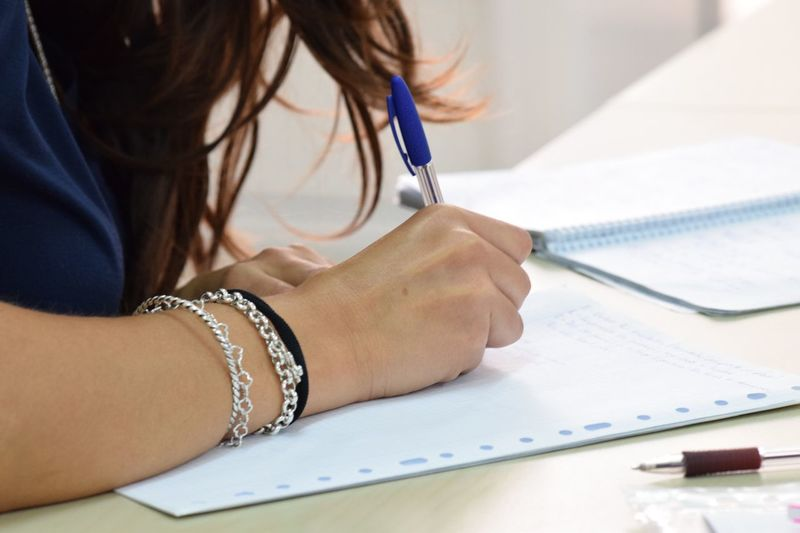 Cropped image of businesswoman writing in book at office