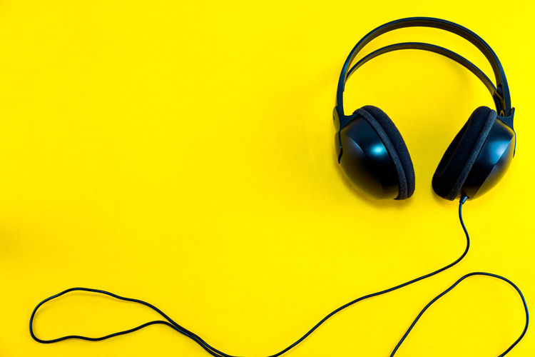 Top view of black headphone against yellow isolated background. Listening music theme. Headphone Music Audio Black Listen Sound HEAD Cable Yellow Isolated Song Stereo Media Karaoke Listening Musical Background Modern Technology Equipment Digital Studio Phones Earphone Close-up Volume Electronics  Portable Device Headset Culture Entertainment Dj Disco Electrical Relaxation Gadget Party Isolation Wire Phone Hear Electric Top View Relax Classic Space Voice Hearing