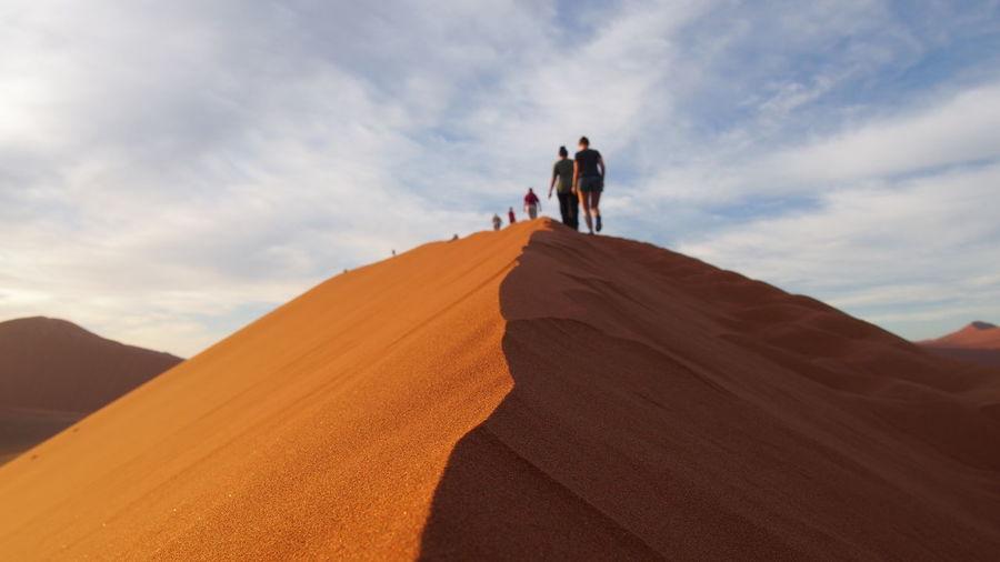 Rear view of people walking on desert against sky