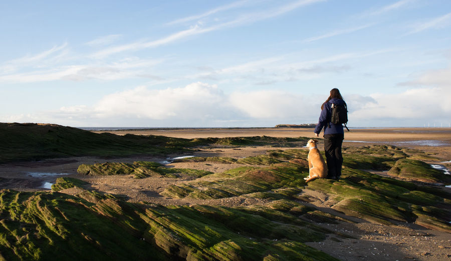 Rear view of young woman with dog standing on landscape against sky