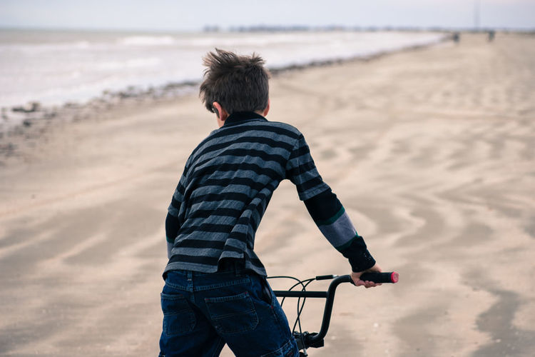 Rear view of boy cycling at beach