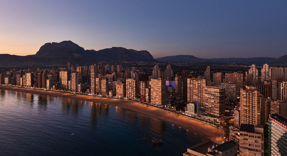 Aerial view of a Benidorm city coastline at sunset. Benidorm is a modern resort city, one of the most popular travel destinations in Spain. Costa Blanca, Alicante province Above Aerial View Alicante, Spain Benidorm Spain City Cityscape Costa Blanca Europe Highrise Illumination Landscape Mediterranean Sea Modern Architecture Mountain Nature Office Building Outdoors Picturesque Skyscrapers SPAIN Street Lights At Sunset Sunset Tourist Resort Travel Destinations Urban Landscape