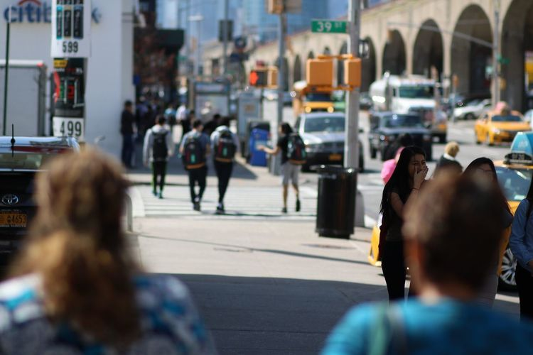 Tilt shift image of people on sidewalk in city