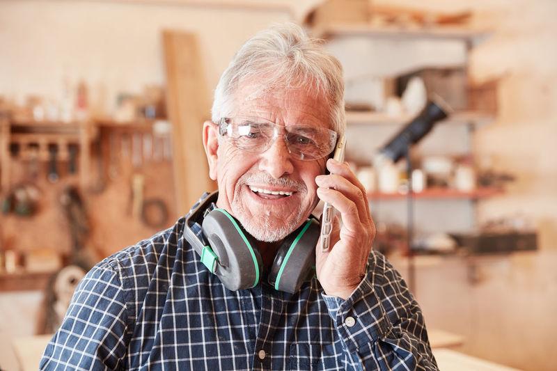 Portrait of smiling carpenter talking on phone at workshop