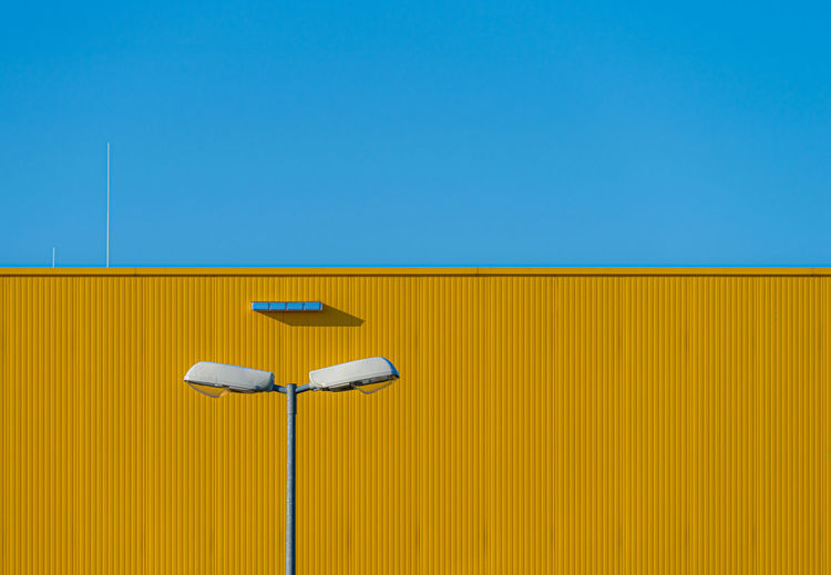 Low angle view of street light against yellow building