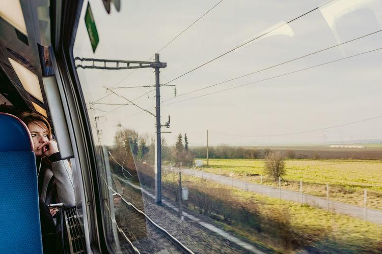 Train by railroad tracks against sky