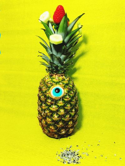 Googly eyes on pineapple over table