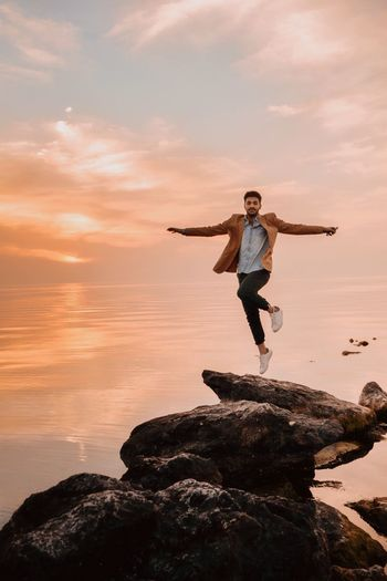 Portrait Of Man Levitating Over Rock At Beach During Sunset