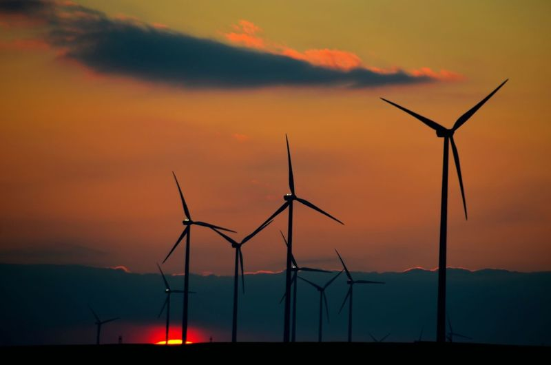 Silhouette windmills against sky during sunset