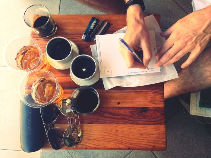 Cropped image of man writing on paper while having coffee
