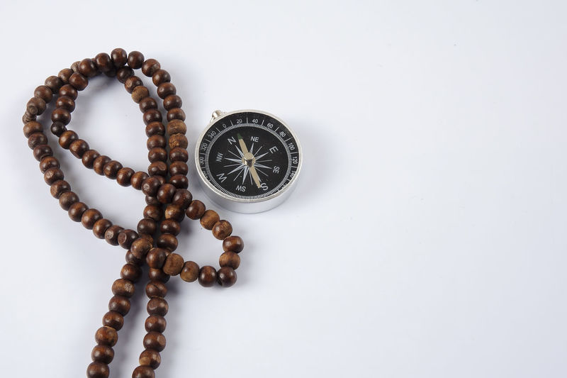 Close-up of compass with bead necklace over white background