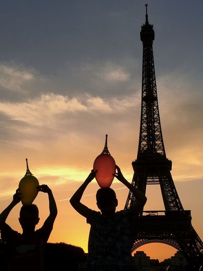 Low angle view of silhouette sibling with balloons near eiffel tower against sky during sunset