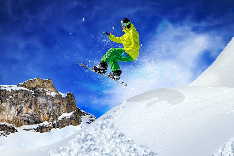 Low Angle View Of Man Snowboarding In Mid-Air Above Snowcapped Mountain