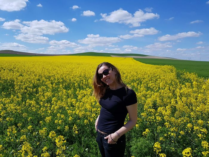 Portrait of woman smiling while standing at rape field against sky
