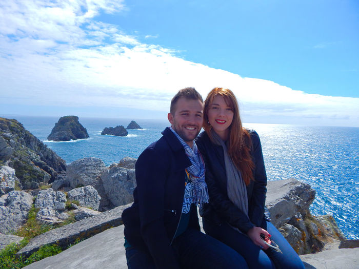 Portrait of smiling couple sitting on rock by sea against sky