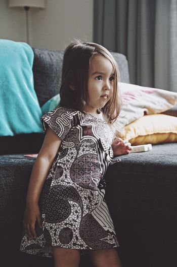 Girl looking away while standing by sofa at home