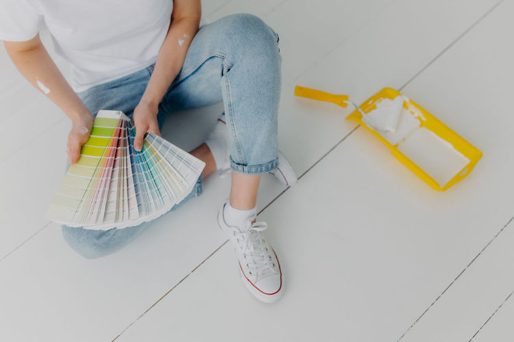 Low section of painter choosing color from swatch