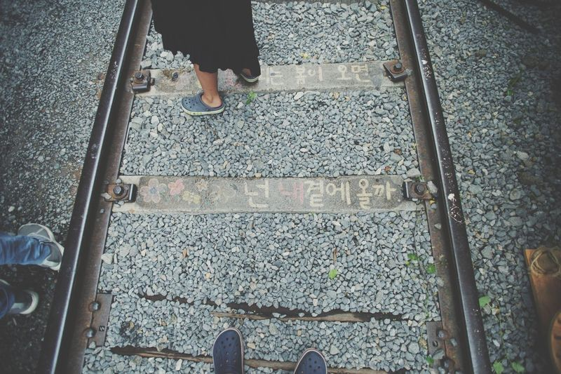 Low section of person standing on railroad track