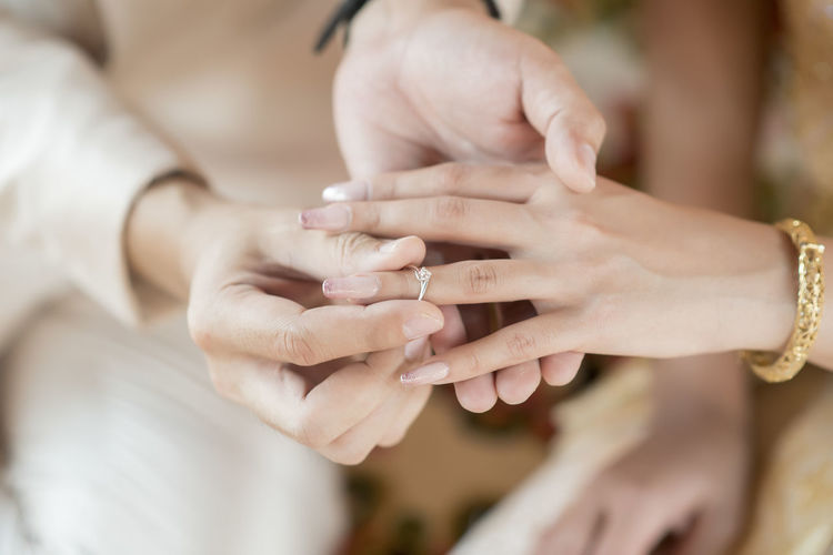 Midsection of groom putting ring in bride finger