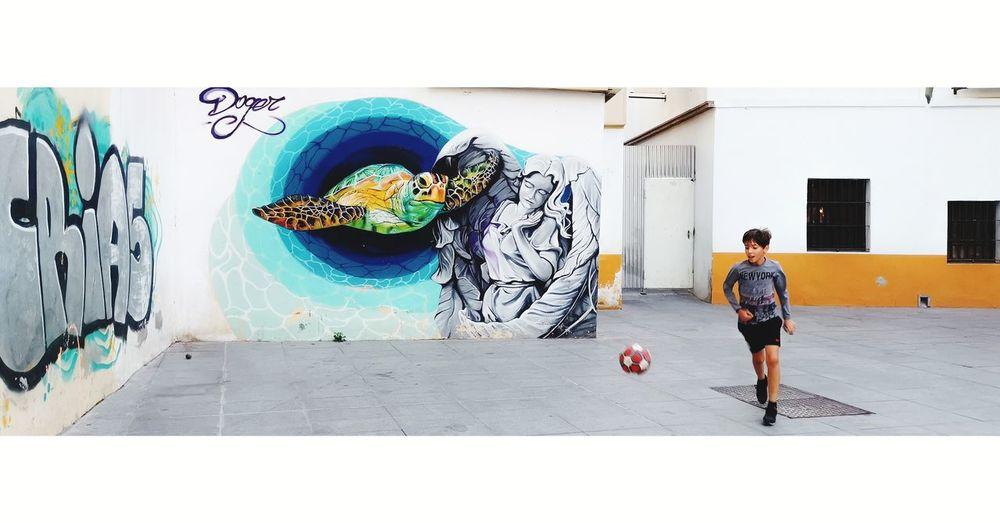 Full length rear view of man walking against graffiti wall