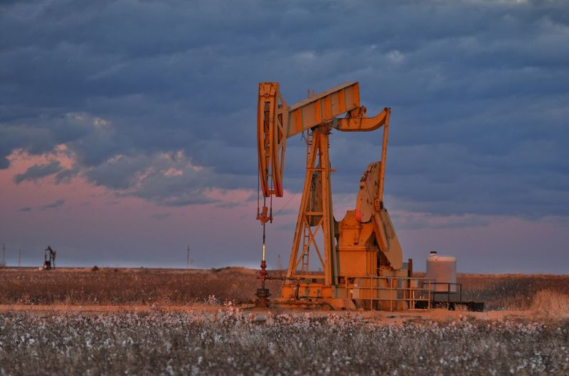 Drilling Rig On Oil Field Against Cloudy Sky During Sunset