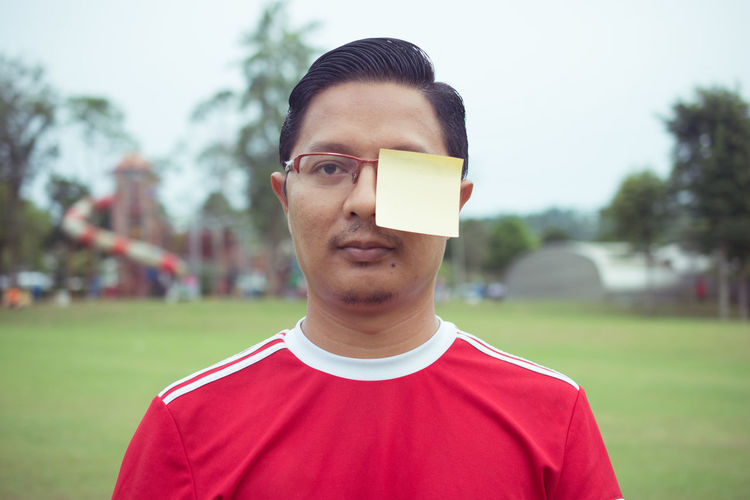 Portrait Of Mid Adult Man With Adhesive Note On Face On Soccer Field