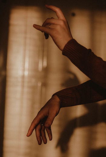 Cropped hand of woman gesturing at home