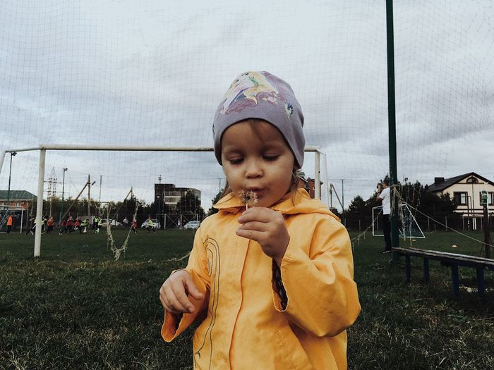 Girl holding ice cream standing outdoors