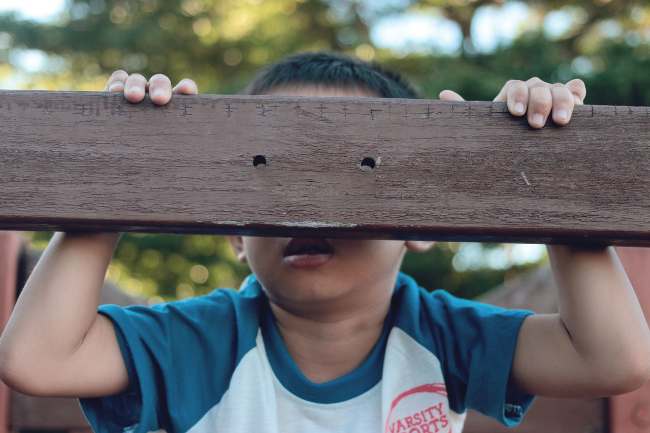 childhood, boys, real people, casual clothing, leisure activity, outdoors, front view, focus on foreground, elementary age, lifestyles, one person, day, playing, wood - material, tree, close-up