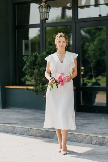 Full length portrait of woman standing by railing