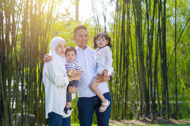 Playful family spending time together at park. Group Of People Men Standing Togetherness Child Males  Childhood Boys Family Three Quarter Length Offspring Smiling Bonding Father Baby Son Emotion Happiness Plant Young Innocence Positive Emotion Outdoors