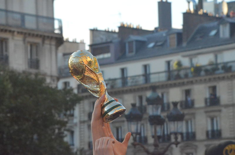 Person holding trophy against buildings in city