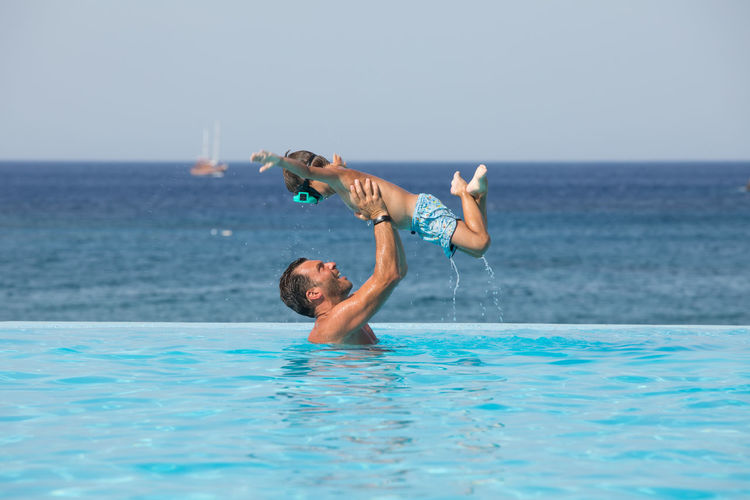 Side view of father holding son in mid air against sea