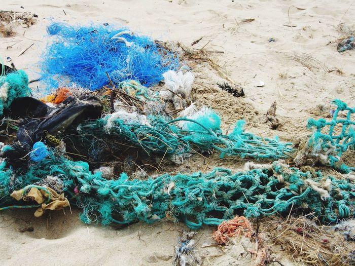 High angle view of messy fishing nets on sand