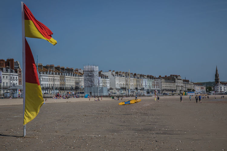 Beach Flags Dorset Coast Dorset,England English Beach Lyme Regis Architecture Beach Building Exterior Built Structure City Clear Sky Copy Space Crowd Day English Coast Flag Incidental People Independence Land National Icon Nature Outdoors Patriotism Sand Sky Surf Lifesaver Travel Water Wind