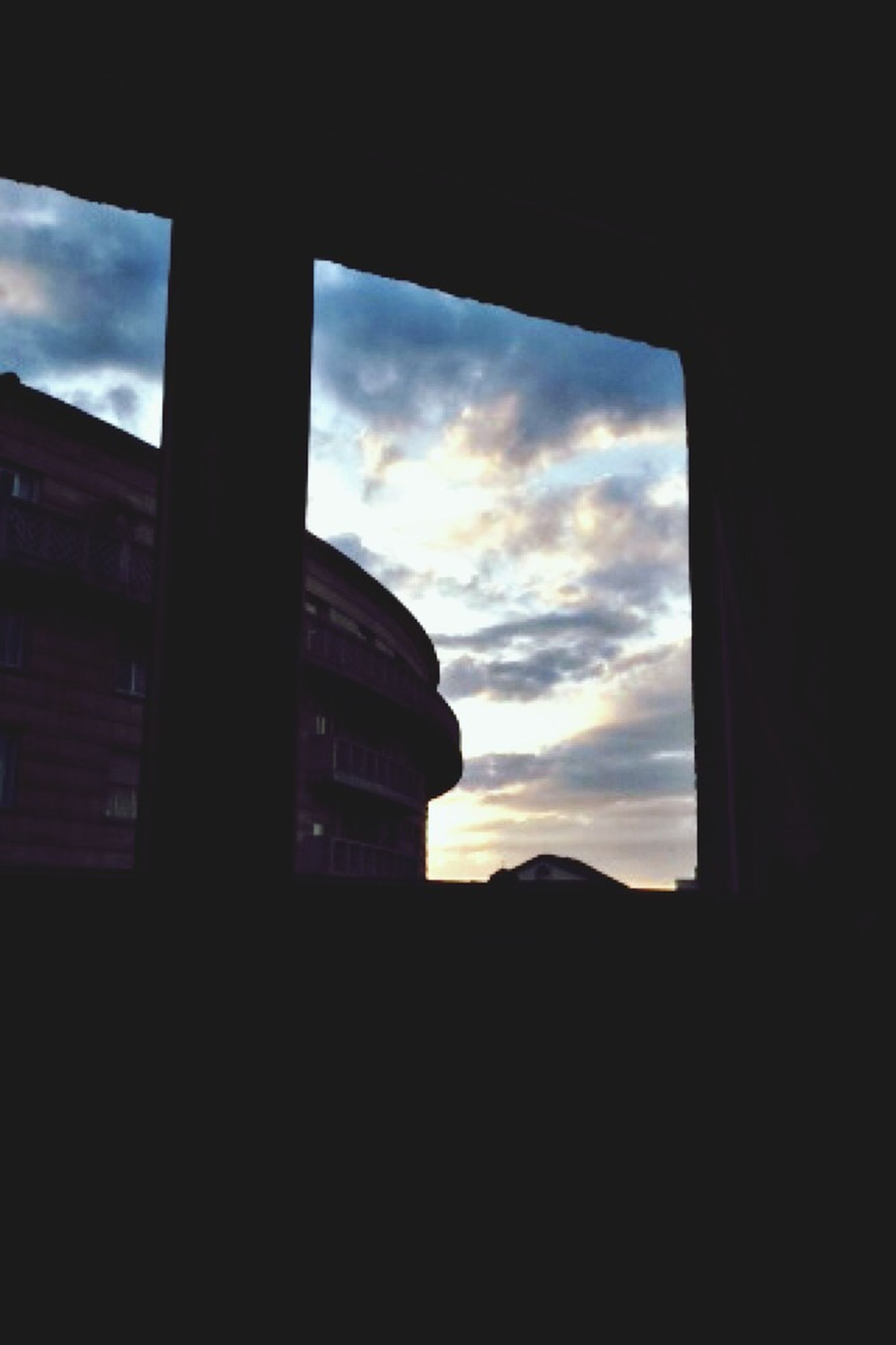 architecture, sky, silhouette, built structure, window, indoors, cloud - sky, dark, building exterior, cloud, sunset, glass - material, building, cloudy, low angle view, no people, transparent, dusk, city, looking through window