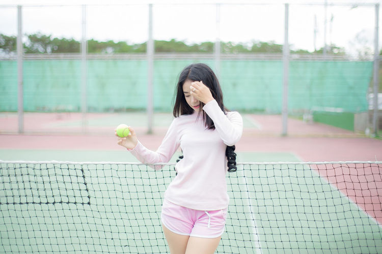 Fashion portrait pretty woman at tennis court. Ball Court Hairstyle Holding Leisure Activity Lifestyles Net - Sports Equipment One Person Real People Sport Standing Tennis Tennis Ball Women