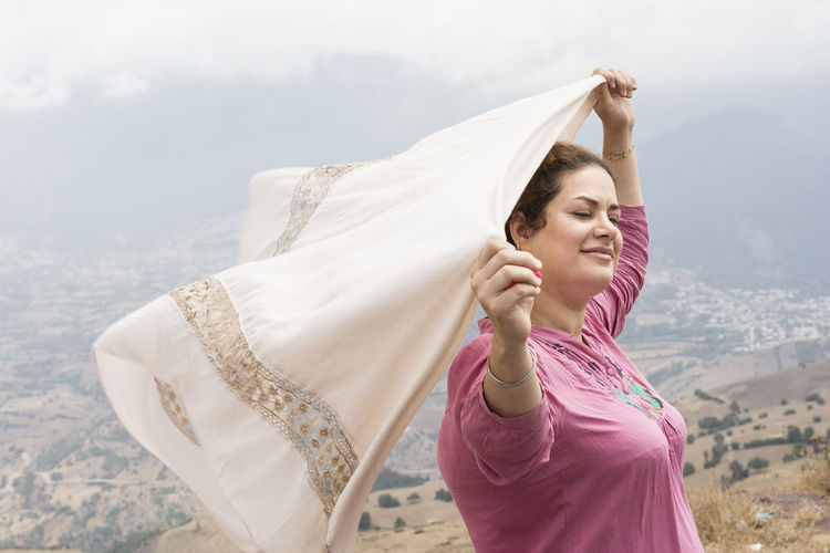 Woman with eyes closed holding aloft scarf while standing on mountain