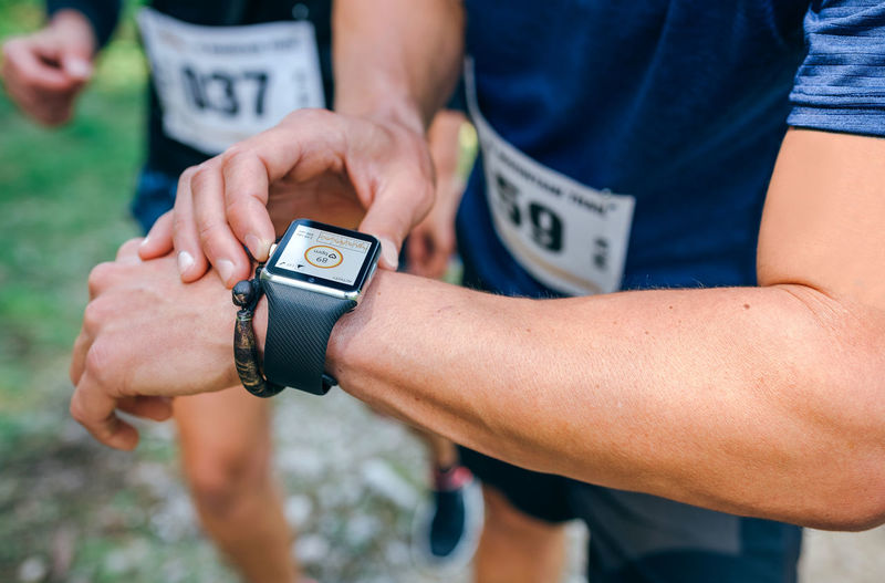 Unrecognizable sportsman looking at a smartwatch during a race Effort Heartbeat Horizontal Marathon Nature Path Running Trees Unrecognizable People Active Adventure Calories Caucasian Competition Course Fitness Forest Outdoors Race Runner Smartwatch Sport Track Trail Watch