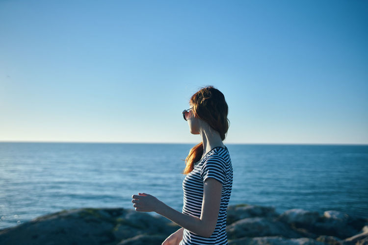 Side view of woman against sea against clear sky