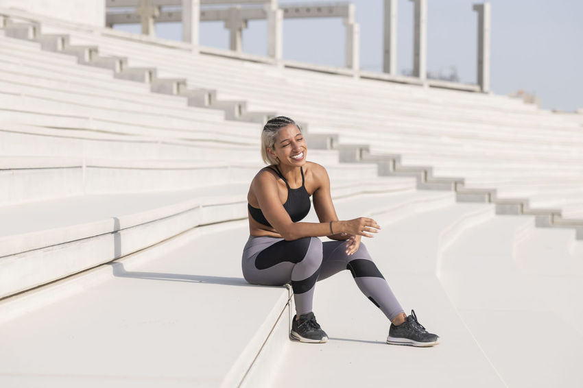 Middle Eastern Girl with short braided hair sitting on the stairs of a construction site wearing gray and black fitness outfit on a hot bright sunny day. Exercising Jumping Off Rocks Sitting Adult Architecture Bright Day Built Structure Day Dusty Exercising Fitness Model Full Length Healthy Lifestyle Hot Day ☀ Leisure Activity Lifestyles Middle Eastern Woman One Person Portrait Real People Side View Sitting Smiling Sport Sports Clothing Staircase Stretching Young Adult