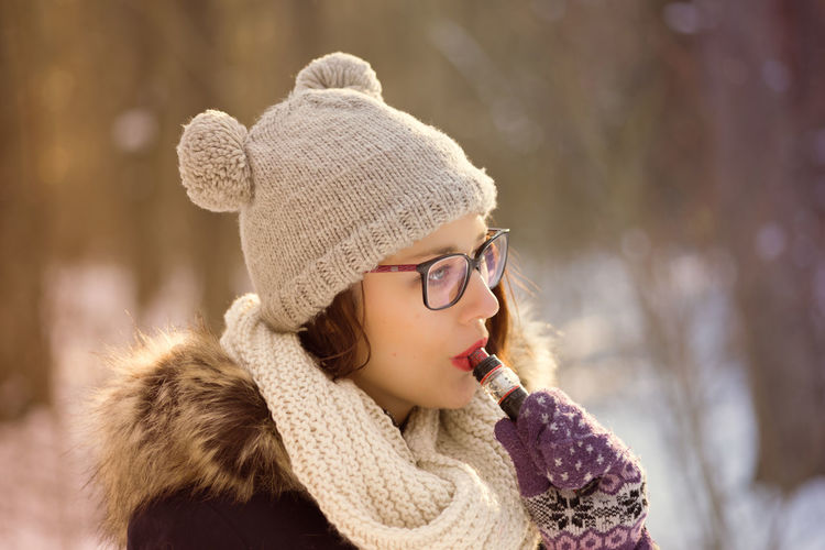 Smoking Beautiful Woman Close-up Cold Temperature Day Fashion Focus On Foreground Fur Fur Coat Glove Knit Hat Lifestyles Nature One Person Outdoors People Real People Scarf Snow Vape Warm Clothing Winter Young Adult Young Women
