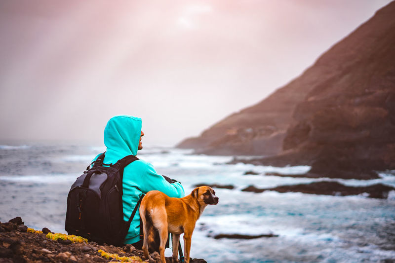 Man with a dog in front of rural coastline landscape with mountains and waves and sun rays comming through the clouds. Santo Antao Island, Cape Verde. Cape Verde Dogs Animal Animal Themes Beauty In Nature Canine Cold Temperature Dog Domestic Domestic Animals Land Looking At View Mammal Mountain Nature One Animal Outdoors Pets Photographer Rear View Scenics - Nature Sky Vertebrate Warm Clothing Winter