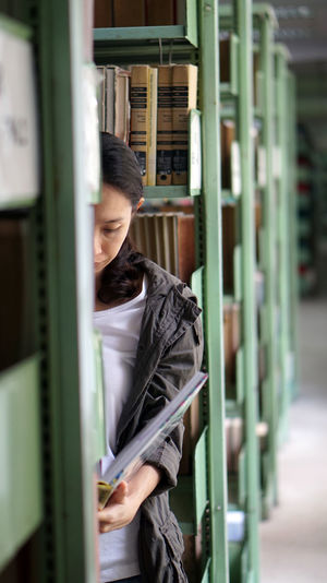 Woman standing amid bookshelf in library