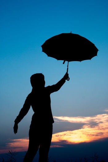 Silhouette Person Holding Umbrella Against Sky During Sunset