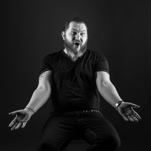 Happy Mid Adult Man Gesturing While Sitting Against Black Background
